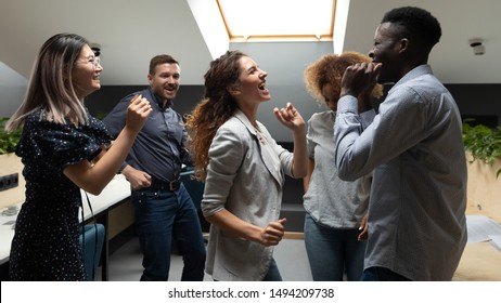 Overjoyed motivated carefree multiracial business team people dancing together in office, happy diverse staff group having fun laughing enjoying corporate party rejoicing success victory win concept