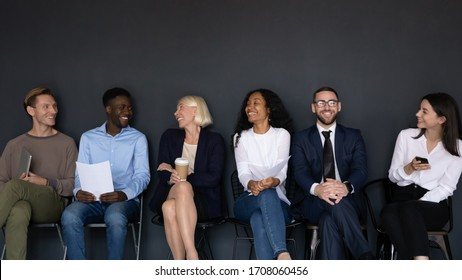 Overjoyed multicultural diverse candidates sit on chairs wait for interview have fun talking, happy multiethnic diverse applicants speak and chat joke laugh before hiring process, employment concept