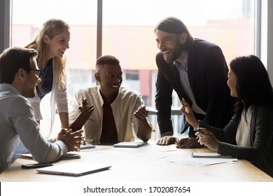 Overjoyed multiracial businesspeople sit at office desk talk laugh negotiating at meeting together, smiling multiethnic diverse colleagues have fun joke discussing ideas at briefing in boardroom