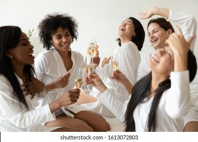Overjoyed multiracial millennial girls in bathrobes drink champagne wine have fun enjoy hen party at home, happy smiling diverse female friends celebrate bachelorette bridal shower together
