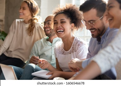 Overjoyed multiracial young people sit in row have fun laughing studying together indoors, happy international diverse students joke chat brainstorm preparing for test making notes learning