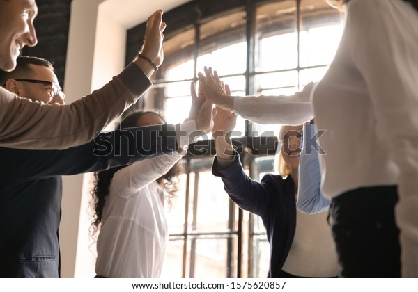 Overjoyed older and younger teammates joining hands in air, giving high five, celebrating shared company success in business meeting. Happy diverse colleagues coming to common decision, showing unity.