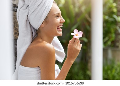 Overjoyed pretty woman spends summer vacations abroad, stays in hotel, rests after taking bath, wears white towel on head, holds beautiful small flower in hand, takes care of her skin and appearance