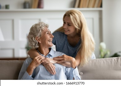 Overjoyed senior 60s mother and adult daughter relax together in living room hugging and cuddling, happy mature mum and grownup girl embrace show love enjoy home family weekend together
