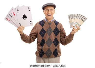 Overjoyed senior holding four aces and bundles of money isolated on white background