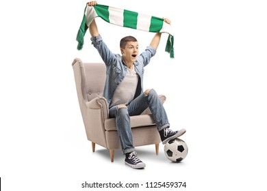 Overjoyed teenage soccer fan with a scarf and a football sitting in an armchair isolated on white background