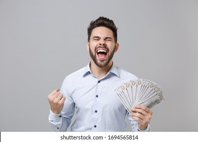 Overjoyed unshaven business man in light shirt isolated on grey background. Achievement career business concept. Mock up copy space. Hold fan of cash money in dollar banknotes doing winner gesture