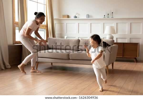 Overjoyed Vietnamese young mom have fun run play with cute smiling biracial daughter in living room, happy Asian mother or nanny involved in family activity with small ethnic girl child at home