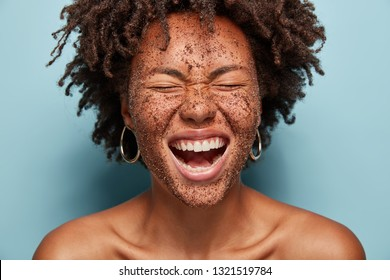 Overjoyed woman laughs loudly, cleans face skin with coffee scrub, has natural mask, crisp hair, poses topless against blue background, squints face, wants to have healthy skin. High resolution