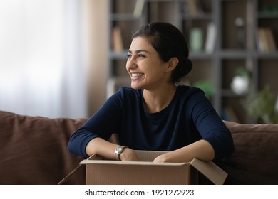 Overjoyed young 20s Indian woman feel excited with good quality order shopping online from home. Smiling millennial ethnic female buyer unbox unpack parcel buying on web. Delivery, shipping concept.