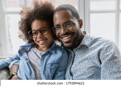 Overjoyed young african American dad and small ethnic daughter hug and cuddle show love and bonding relationship, smiling biracial father and little girl child embrace enjoy family weekend together