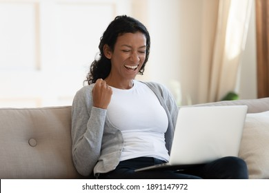 Overjoyed young african american woman making yes gesture, looking at computer screen, celebrating winning online lottery or reading email with amazing unbelievable news or getting dream job offer.