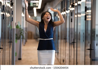 Overjoyed young Asian businesswoman have fun celebrate business success work promotion in corridor, excited ethnic millennial female employee scream jump from happiness, perform winner dance