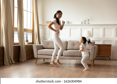 Overjoyed young Asian mom and cute little biracial daughter have fun dancing in living room together, happy millennial mother play involved in funny activity with small Vietnamese girl child at home