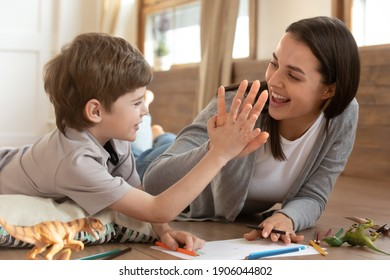 Overjoyed young Caucasian mother and small son give high five celebrate good result have fun drawing together. Smiling mom or nanny painting at home make deal with little boy child. Hobby concept.
