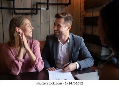Overjoyed young couple sit in cafe meeting with consultant or realtor closing deal, happy excited husband and wife sign paper document make agreement with real estate agent in coffeeshop