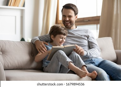 Overjoyed young father and little preschooler son rest on sofa in living room have fun reading book together, smiling dad and small boy relax on couch at home laugh enjoying funny story in textbook