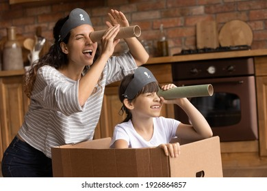 Overjoyed young Hispanic mother and little 7s daughter have fun playing pirates game at home together. Playful happy Latino mom or nanny and small girl child engaged in funny activity on weekend.