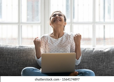 Overjoyed young indian woman celebrating personal achievement, sitting with computer on couch at home. Happy euphoric millennial girl getting grant university scholarship or employment notification.