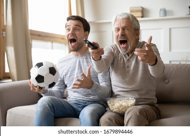 Overjoyed young man relax on sofa in living room with senior father scream support favorite sports team together, excited mature dad rest with grown-up adult son watch football match on TV at home