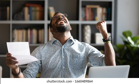 Overjoyed young mixed race man in glasses holding paper in hands, celebrating unbelievable triumph, sitting at workplace. Excited happy millennial african american businessman received loan approval.
