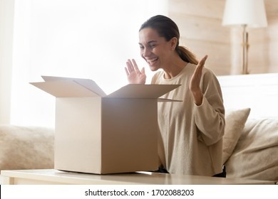 Overjoyed young mixed race woman opening carton box, purchase from online store. Happy female client satisfied with fast delivery service, unpacking cardboard parcel, internet shopping concept.