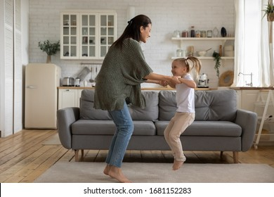 Overjoyed young mother have fun dancing with excited little cute daughter enjoying weekend at home, happy mom playing with funny preschooler girl child jumping involved in activity together