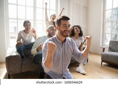 Overjoyed young multiethnic people gather indoors watch football match online on TV supporting favorite team, excited multiracial millennial friends sport fans enjoy game scream celebrating victory