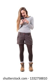 Overjoyed young stylish woman screaming while reading and holding mobile phone. Full body isolated on white background.