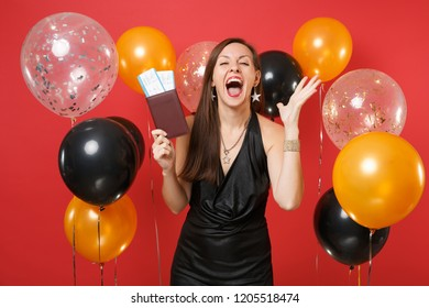 Overjoyed young woman in black dress holding passport, boarding pass tickets, spreading hands, screaming on bright red background air balloons. Happy New Year, birthday mockup holiday party concept