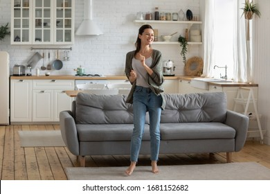 Overjoyed young woman enjoy free leisure weekend at home dancing listen to music in living room, smiling happy millennial female have fun moving to rhythm being active in modern studio home