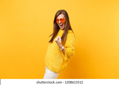 Overjoyed young woman in fur sweater, heart orange glasses screaming doing winner gesture saying Yes isolated on bright yellow background. People sincere emotions, lifestyle concept. Advertising area