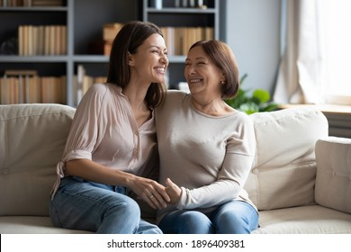 Overjoyed young woman with mature mother chatting, laughing at joke, enjoying pleasant conversation, middle aged mum and grownup daughter hugging, having fun, sitting on cozy couch at home