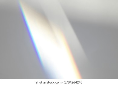 Overlay effect for photo and mockups. Organic drop diagonal shadow and ray of light with rainbow from window on a white wall.