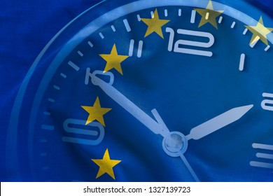 Overlay of the EU flag and the dial of a clock with hands and numerals showing five to twelve in a conceptual image full frame background