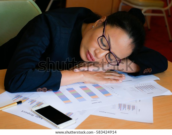 an overload business employee is tried and sleeps on the desk during her working time.