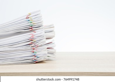 Overload paperwork report of sale and receipt with colorful paper clip on wooden table with white background and copy space. Stack document is high as work hard. Business and finance concept success.