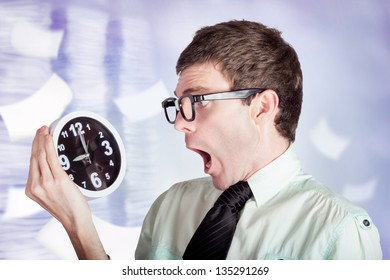 Overloaded businessman standing in a modern office flooded with paper work holding over time clock with look of stress