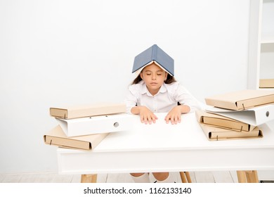 Overloaded with tasks. Girl child exhausted book roof head white background. Schoolgirl tired of reading and studying. Kid school uniform tired sleepy face. Schoolgirl fall asleep while studying.