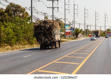 an overloaded thai truck transporting hay in a thai road, Thailand