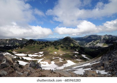 Overlook at Mount Rainier National Park in springtime with mountain peaks backed by blue skies.