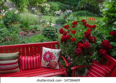Overlooking a colorful backyard garden with casual red furniture and geraniums.in the foreground.