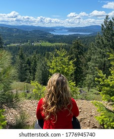 Overlooking Lake Coeur d'Alene in Idaho after hiking up the hills; spring day with beautiful blue skies and white clouds; mountains and greenery in the distance