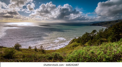 Overlooking the Muir Woods Beach area in Northern California, near San Francisco.  The clouds cast a dramatic shadow on the ocean below, and lush foliage frames the foreground.
