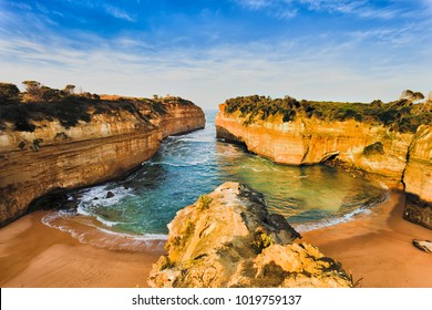 Overlooking secluded tiny Loch Ard Gorge beach in Twelve Apostles marine park on Shipwreck coast of Victoria, Australia. Warm morning light illuminates limestone cliffs and sand.