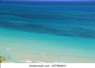Overlooking a tropical paradise scenic two-toned blue and turquoise colored water from above or a top view. People on vacation staying at the resorts enjoying swimming in the shallow warm water.
