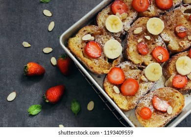 Overnight baked French toast topped with berries bananaa and nuts, overhead view