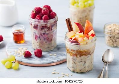 Overnight oats, bircher muesli with raspberry, apple in glass jars on wooden background.