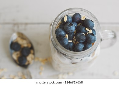Overnight oats with blueberry on wooden table. Homemade yogurt with whole grain oats. Healthy breakfast recipe