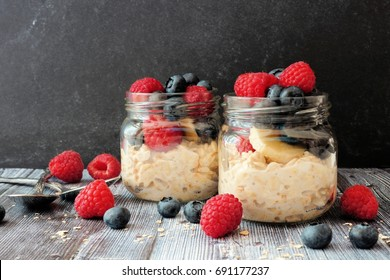 Overnight oats with fresh blueberries and raspberries in jars on a rustic dark background